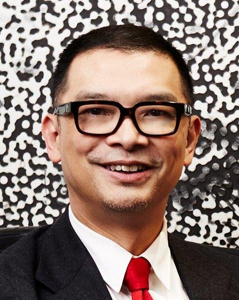 Portrait of Dr Dick Quan in front of artwork