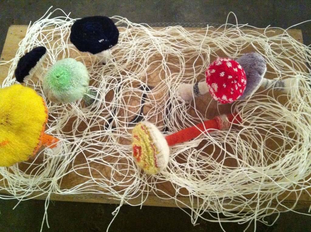 Knitted mushrooms with mycelia made from string.